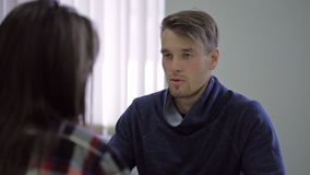 Young male consultant talking with his client, in. Proficient young male employee in a comfortable shirt, is talking to his female client and discuss problems stock video footage