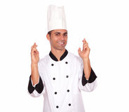 Young male cook crossing fingers while standing Stock Images