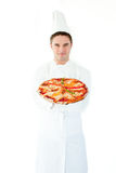 Young male cook presenting a pizza Royalty Free Stock Images