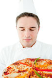 Young male cook smelling at pizza with closed eyes Stock Photography