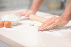 Young male cook is stretching the dough thoroughly. Pastry making. Young athletic male cook occupied with stretching freshly made dough for baking pastry Stock Photography