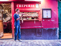 Young male cook twirls crepe pan in front of his creperie on Montmartre Royalty Free Stock Photos