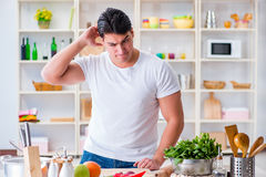 The young male cook working in the kitchen Stock Photography