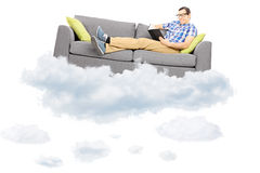 Young male on a couch reading a book and floating on a cloud Royalty Free Stock Photo