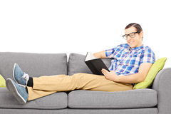 Young male on a couch reading a book Royalty Free Stock Photography