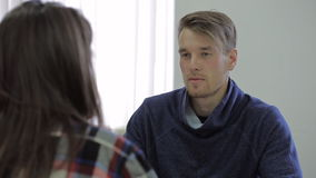 Young male counselor asks questions to his client. Proficient young male employee in a comfortable shirt, asking questions with his female client and discuss stock footage