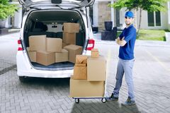 Courier with pile of package and van. Young male courier standing near a pile of package with a dolly and van Royalty Free Stock Photo