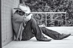A young male cowboy. A young cowboy rests his head against a wall this photo is black and white stock image