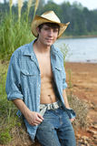 A young male cowboy. A young attractive man dressed as a cowboy smiling at the camera outside stock photo