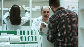 Young male customer buy medical products in a drugstore. Professional shot in 4K resolution. 081. You can use it e.g. in your commercial video, business Stock Photos