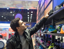Young male customer choosing sneakers. Portrait of young male customer choosing black sneakers at supermarket store. He is taking shoes from upper shelf Royalty Free Stock Photos