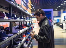 Young male customer choosing sneakers. Portrait of young male customer choosing sneakers at supermarket store Royalty Free Stock Images