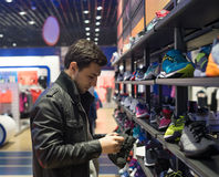 Young male customer choosing sneakers. Portrait of young male customer choosing sneakers at supermarket store Royalty Free Stock Photo