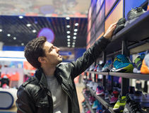 Young male customer choosing sneakers. Portrait of young male customer choosing sneakers at supermarket store. He is taking shoes from she shelf Royalty Free Stock Photography