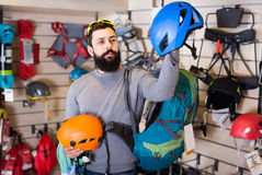 Young male customer examining helmets in sports equipment store Royalty Free Stock Images