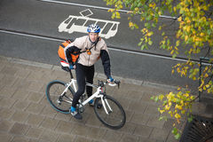 Young Male Cyclist With Backpack On Sidewalk Stock Photo