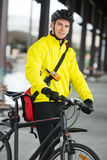 Young Male Cyclist With Bag. Portrait of young male cyclist in protective gear with bag Stock Photo