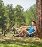 Young male cyclist resting by a tree in park. With his bicycle beside him shot with tilt and shift lens Royalty Free Stock Images