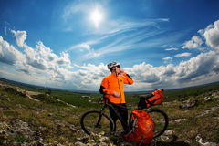 Young Male Cyclist Talking On Cell Phone. Young Man Cyclist in Orange Clothes Talking On Cell Phone Against Blue Sky Royalty Free Stock Photography