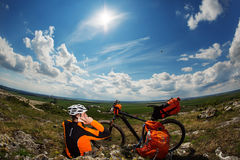 Young Male Cyclist Talking On Cell Phone. Young Man Cyclist in Orange Clothes Talking On Cell Phone Against Blue Sky Stock Photo