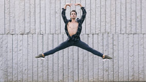 Young male dancer performing ballet moves. Isolated on a grey wall dressed in casual clothes Royalty Free Stock Photos
