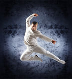 A young male dancer performing in white clothes. A young and sporty modern dancer in white clothes. The image is taken on a dramatic background Royalty Free Stock Image