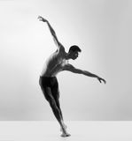A young male dancer posing on a grey backgroun Royalty Free Stock Images