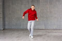 Young male dancer posing on studio background. Modern style dancer young man working out wearing casual red sweater and jeans Stock Images