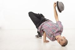 Young male dancer sitting on his head with hat up. Young man wearing casual shirt dancing sitting on one hand, performing breakdance moves upside down, with head Royalty Free Stock Photography