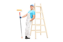 Young male decorator holding a paint roller Stock Photography