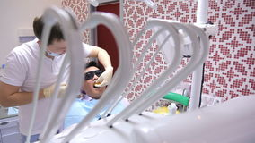 Young male dentist and nurse make a mold of patient's teeth lying in chair. stock video footage