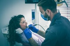 Young male dentist surgery female patient. Dentist men working in his office stock images
