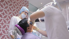 Young male dentist treats patient's teeth using dental unit under supervision of a nurse. stock video