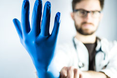 Young Male Doctor with blue glove Stock Images