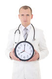 Young male doctor with clock isolated on white Royalty Free Stock Photography