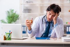 The young male doctor drinking in the office stock images