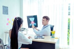 Young male doctor explains a sick patient to listen.Examining checking chest x-ray radiography film of patient at ward hospital. Medical surgery and orthopedics stock photos
