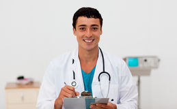 Young male Doctor holding a clip board royalty free stock images