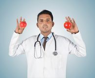 Young male doctor holding a red apple Royalty Free Stock Images