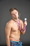 Young male doctor listening at stethoscope while hamming Royalty Free Stock Photos