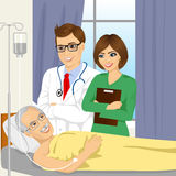 Young male doctor and nurse visiting a senior old man patient Royalty Free Stock Images