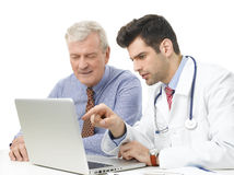 Young male doctor with old patient Royalty Free Stock Image