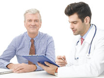 Young male doctor with old patient Stock Photography