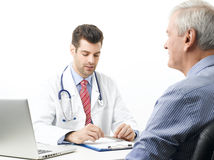 Young male doctor with old patient Royalty Free Stock Photo