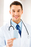 Young male doctor with pack of pills Stock Images