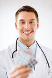 Young male doctor with packs of pills Royalty Free Stock Photos