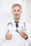 Young male doctor with packs of pills Stock Images