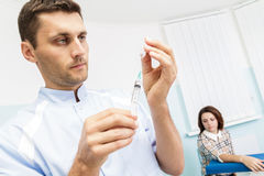 Young male doctor prepares a medicine into the syringe in the office.Doctor holding a syringe Royalty Free Stock Photography
