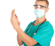 Young male doctor preparing injection. Young male doctor in green workwear and medical mask preparing injection Stock Image