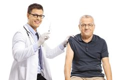 Young male doctor preparing a vaccine for a mature male patient royalty free stock photos